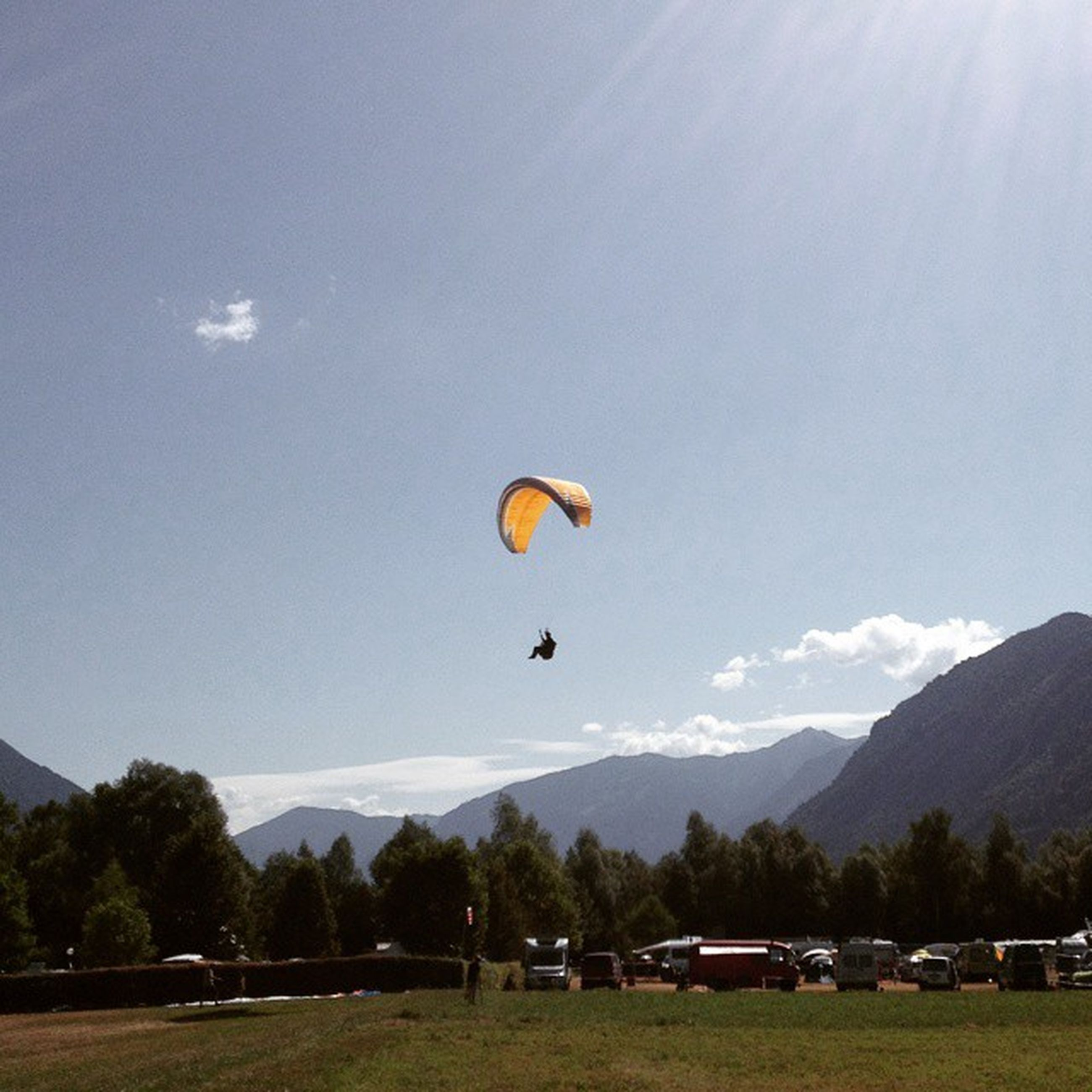 transportation, mid-air, flying, parachute, mountain, extreme sports, mode of transport, paragliding, adventure, sky, hot air balloon, landscape, leisure activity, sport, mountain range, air vehicle, travel, on the move, cloud - sky