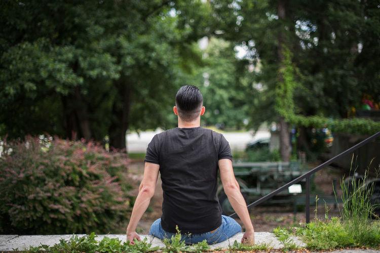 Rear view of man sitting in yard
