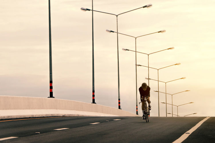 Architecture Bicycle Direction Full Length Land Vehicle Leisure Activity Lifestyles Men Mode Of Transportation Nature One Person Outdoors Real People Rear View Riding Road Sign Sky Street The Way Forward Transportation