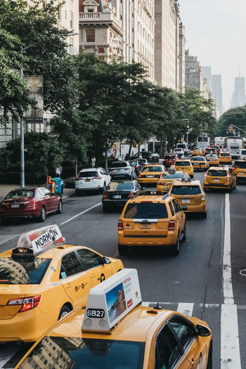 Numerous yellow taxis on a street in Manhattan, New York, USA. New York New York City USA United States Travel Tourism Car City Building Exterior Road City Life Taxi Day City Street No People Yellow Manhattan Many Taxi Travel Destinations NYC NYC Street Holiday Vacations Commute