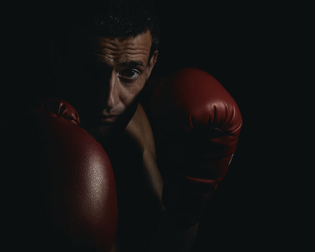 Close-up portrait of boxer against black background
