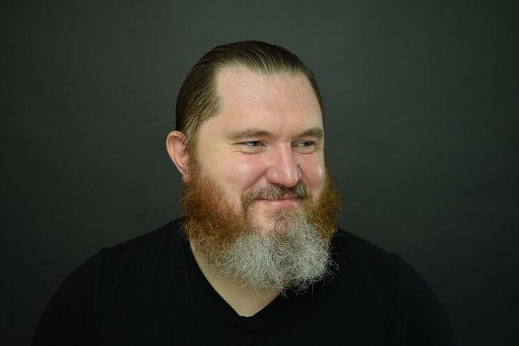 Portrait of smiling man against black background