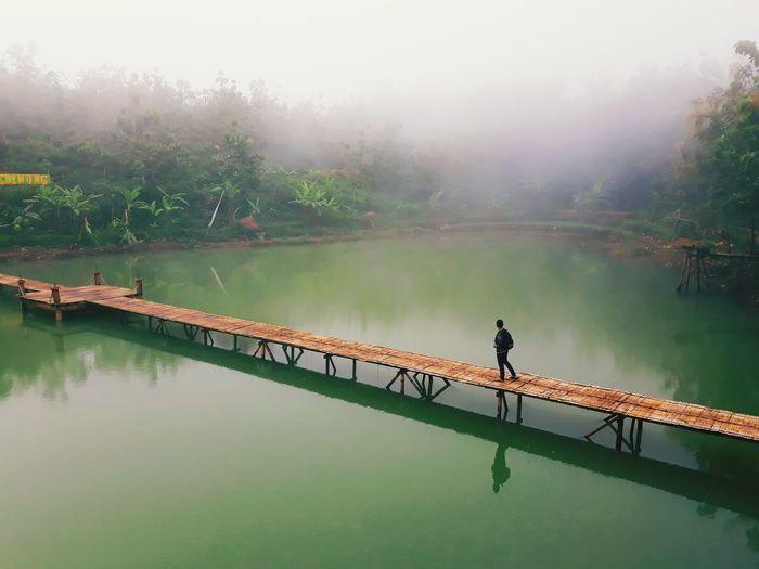 Person walking on footbridge over lake