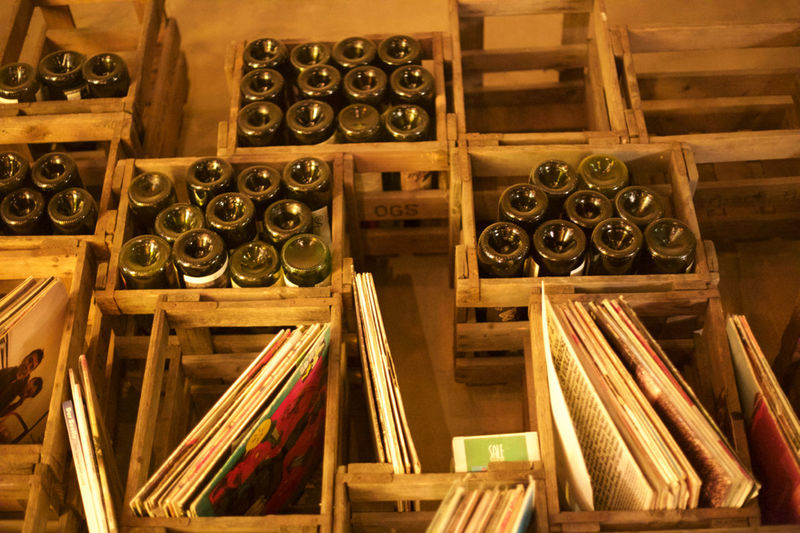 High angle view of wine bottles and books in wooden crates