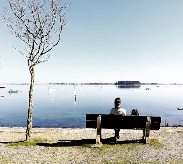 Man sitting on bench by lake against sky