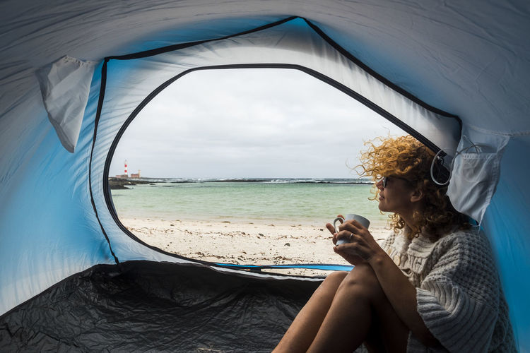 lonely beautiful woman sitting on the tent looking outside. wind on the hair and camping on the beach near the colors of water and shore. freedom and alternative tiny house for traveler lady drinking tea and enjoyed the summer Camping Coastline Lifestyle Beach Blue Break Coffe Day Holding Leisure Activity Lifestyles Mobile Phone Mug One Person Outdoors Sea Sitting Sky Technology Tent Water Wireless Technology Women Young Adult Young Women
