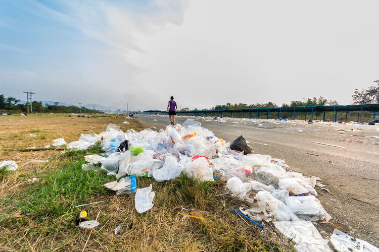 Rear View Of Man Running By Garbage At Parking Lot