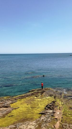 Mid distance view of man standing on rock by sea against blue sky