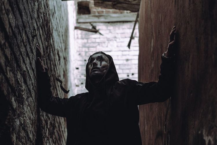 Man with face paint standing in alley