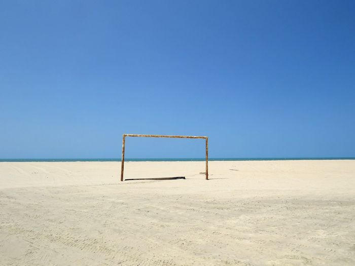 View of goal post on beach against sky