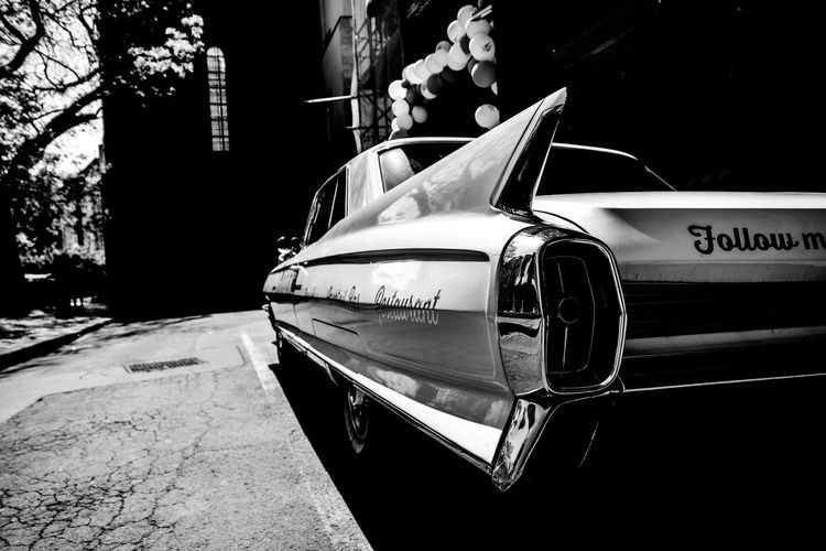 Architecture Building Exterior Built Structure Car City Day Land Vehicle Luxury Mode Of Transportation Motor Vehicle No People Outdoors Retro Styled Road Street Sunlight Text Transportation Tree Western Script