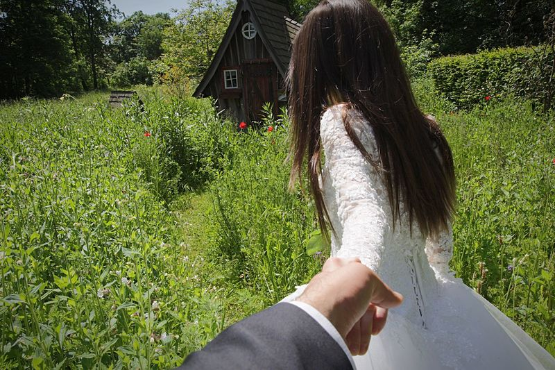 Cropped Image Of Bridegroom Holding Bride Hand On Field