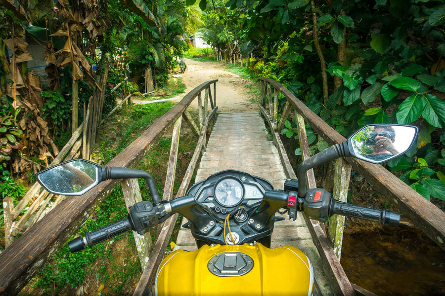 Yellow motorcycle crossing a narrow wooden jungle bridge Bucket List Island Adventure Island Beach Island Beauty Island In The Sun Island Paradise Island Vacation Island View  Islands It's More Fun In The Philippines Jungle Jungle Bridge Motorbike Motorcycle Motorcycle Adventure Motorcycle Trip Off Road Philippines Philippines Photos Road Bike Rustic The Philippines Touring Women Wooden Bridge