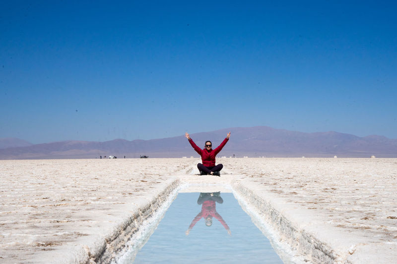 Woman with arms raised reflecting in water while sitting at salt flat
