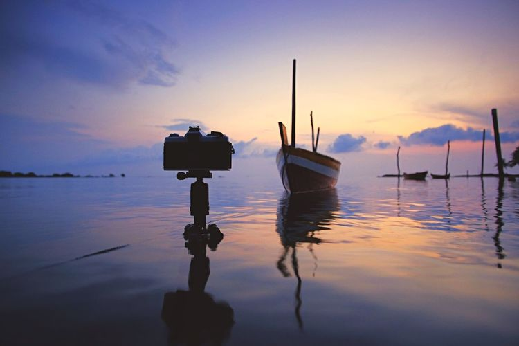 Camera On Tripod Against Moored Boats In Sea At Sunset