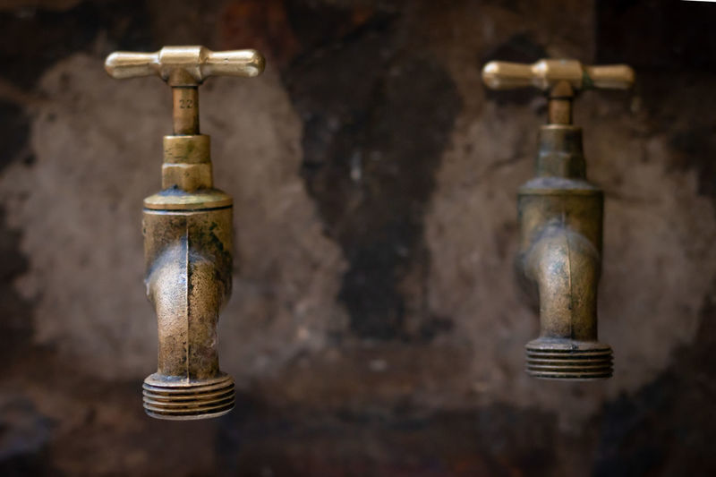 Close-up of faucets against wall