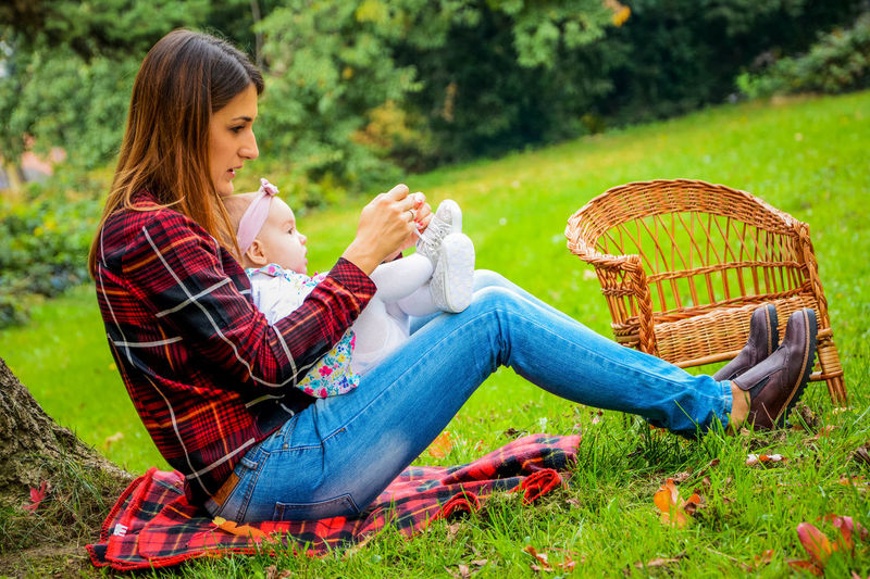 Adult Basket Casual Clothing Day Eating Family With One Child Food Food And Drink Full Length Grass Healthy Eating Leisure Activity Nature Outdoors People Picnic Picnic Basket Picnic Blanket Relaxation Sandwich Side View Sitting Togetherness Women Young Women