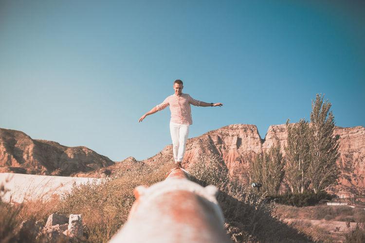 Man Walking On Railing Against Sky