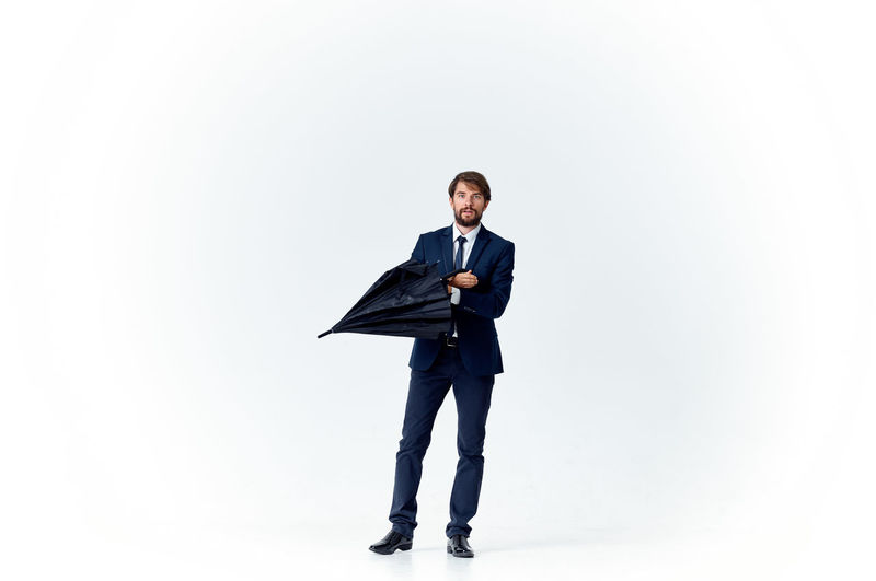 Full length of young man standing against white background