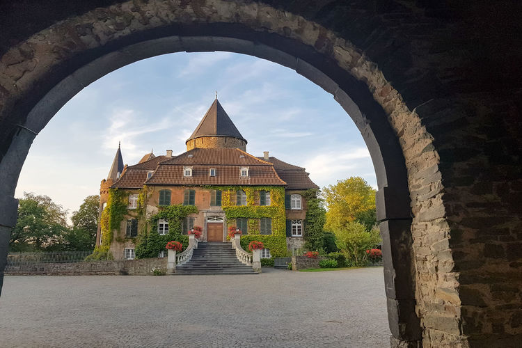 Old moated castle overgrown with ivy. Photographed by a door arch Architecture Built Structure Building Exterior Building Sky Religion Arch Place Of Worship Belief Cloud - Sky Nature Spirituality Day History The Way Forward The Past No People Travel Destinations