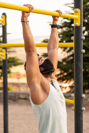 Athletic male exercising chin-ups in playground
