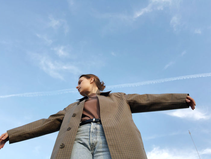 Low angle view of young woman looking away against sky