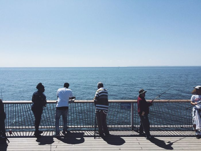 People fishing against railing by sea