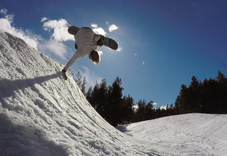 Rear view of man performing stunt while snowboarding on snow covered field