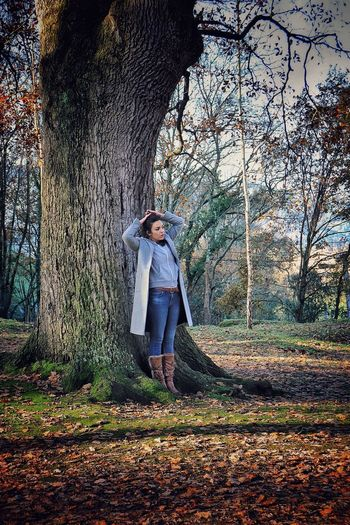 Full Length Of Woman Standing Against Trees In Forest