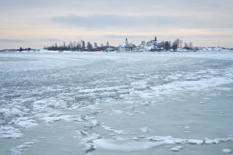 Frozen Sea By Buildings Against Sky During Winter