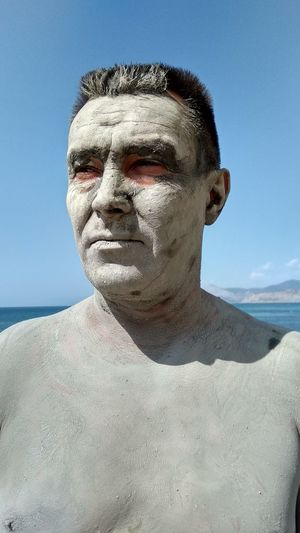 Shirtless man with mud mask standing at beach against sky