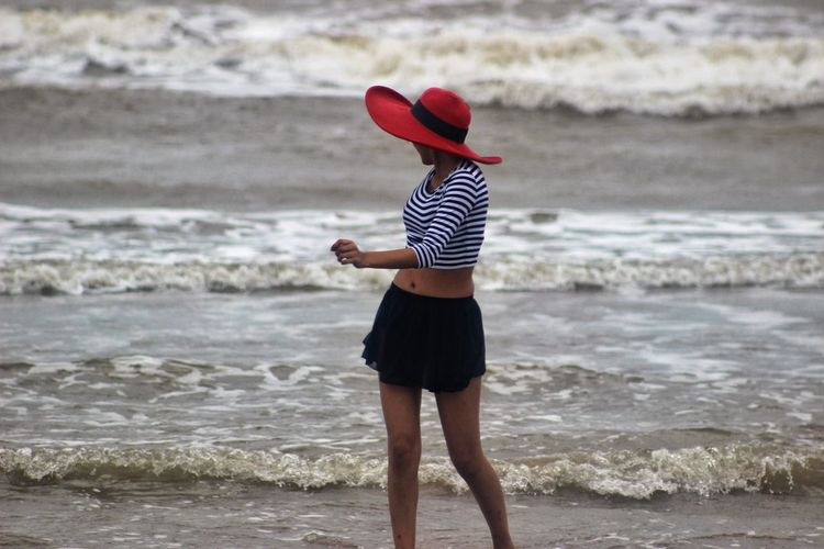 Woman looking at sea waves while walking on shore