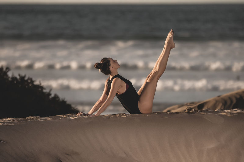 Side view of woman sitting on sand with legs raised training yoga in sunlight on coastline Yoga Woman Beach Copy Space Asana Freedom One Person Sea Young Adult Lifestyles Leisure Activity Real People Young Women Clothing Full Length Land Beauty Bikini Adult Nature Water Sky Beautiful Woman Outdoors