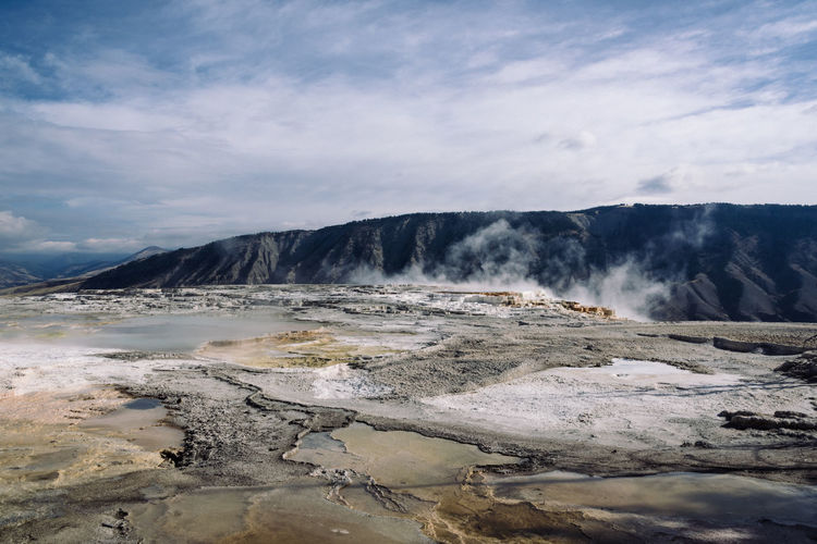 Idyllic shot of hot spring landscape against sky at yellowstone national park