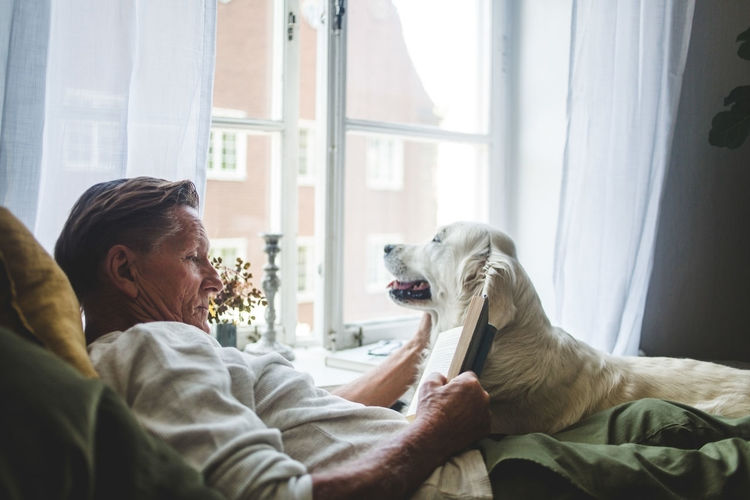 Midsection of man with dog sitting at home