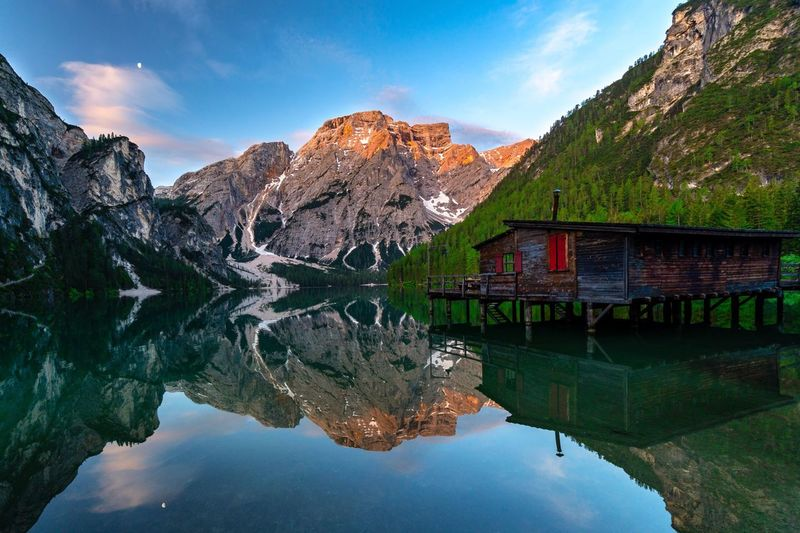 Scenic view of calm lake with stilt house and mountains reflection