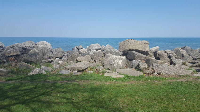 Lakefront Land Water And Sky Beauty In Nature Clear Sky Horizon Over Water Lakeshore Rocks On The Shore Scenics - Nature Tranquility
