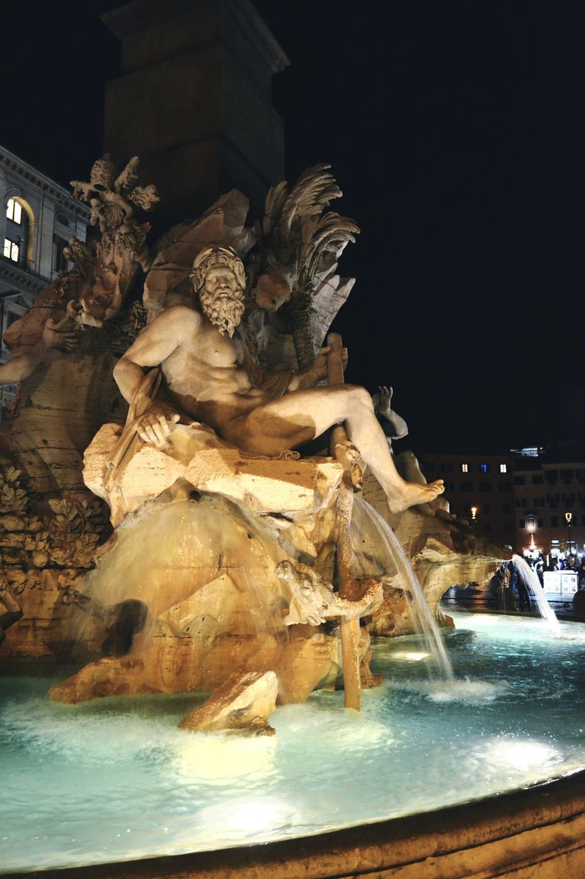 statue, sculpture, building exterior, night, art and craft, human representation, architecture, fountain, built structure, water, outdoors, city, motion, travel destinations, illuminated, no people, sky