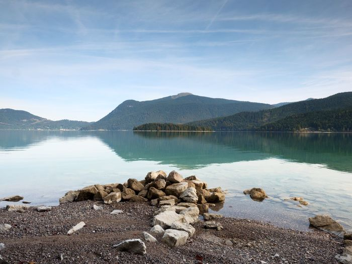 Big boulders sticking out from smooth lake water level. green blue water, mountain in water mirror.