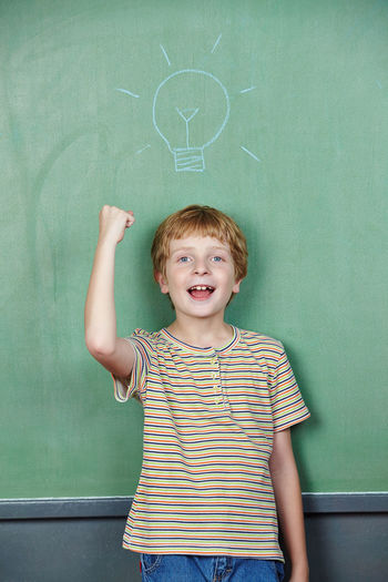 Portrait of boy standing against blackboard with lightbulb drawing at classroom