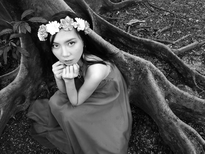 High angle portrait of woman wearing flowers while sitting by tree trunk