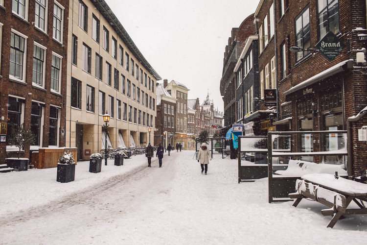 Snow covered street amidst buildings in city