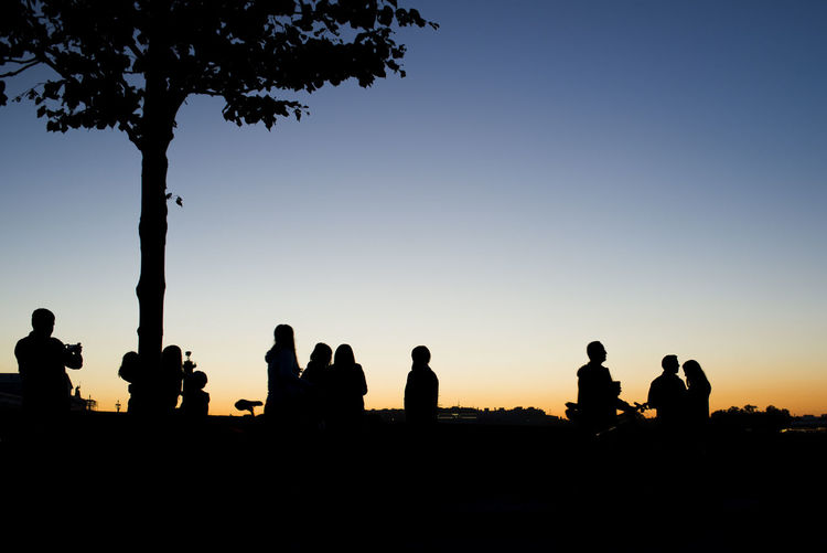 Humanscape Cityscape Clear Sky Copy Space Group Of People Leisure Activity Lifestyles Medium Group Of People Outdoors People Real People Silhouette Sky Standing Sunset Tree