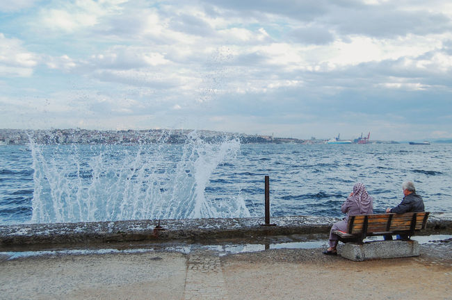 Older couple sitting on the bench by the Bosporus watching waves break Beauty In Nature Cloud - Sky Copy Space Day Force Headscarf Horizon Over Water Lifestyles Mature Adult Men Motion Nature Older Couple Outdoors People Power In Nature Real People Scenics Sea Sitting Sitting On The Bench Sky Water Wave