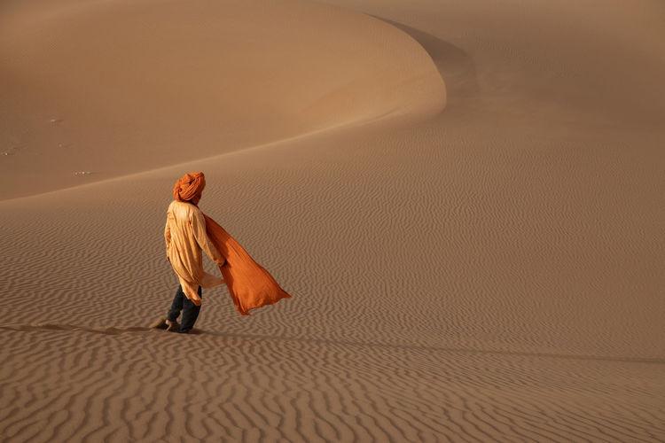 Man walking on sand dune in desert