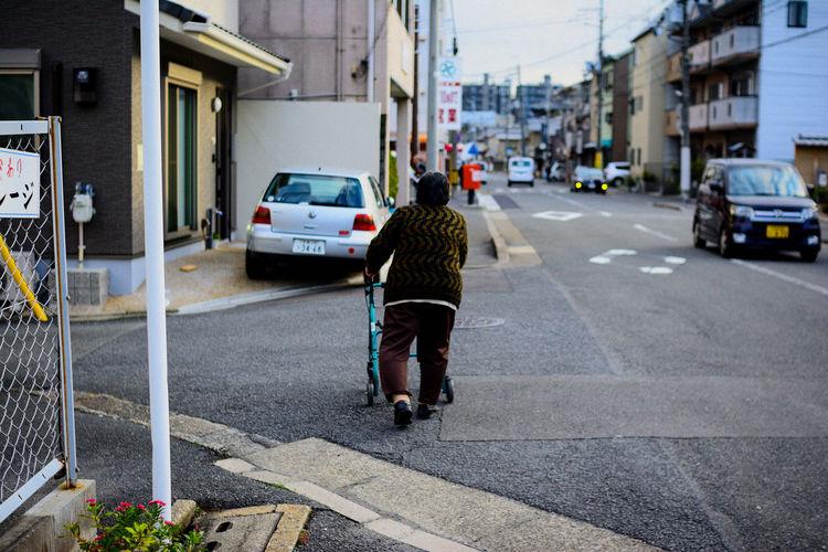 Rear View Of Woman Walking On City Street