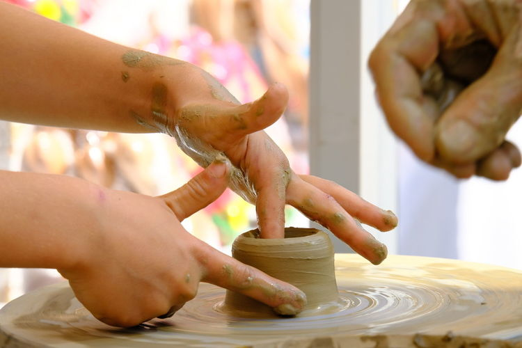 Cropped hands of person molding shape on pottery wheel
