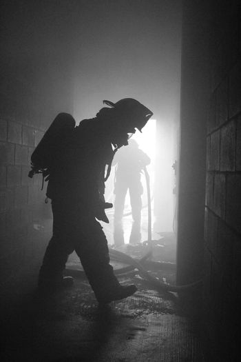 Full length of silhouette firefighters abandoned building