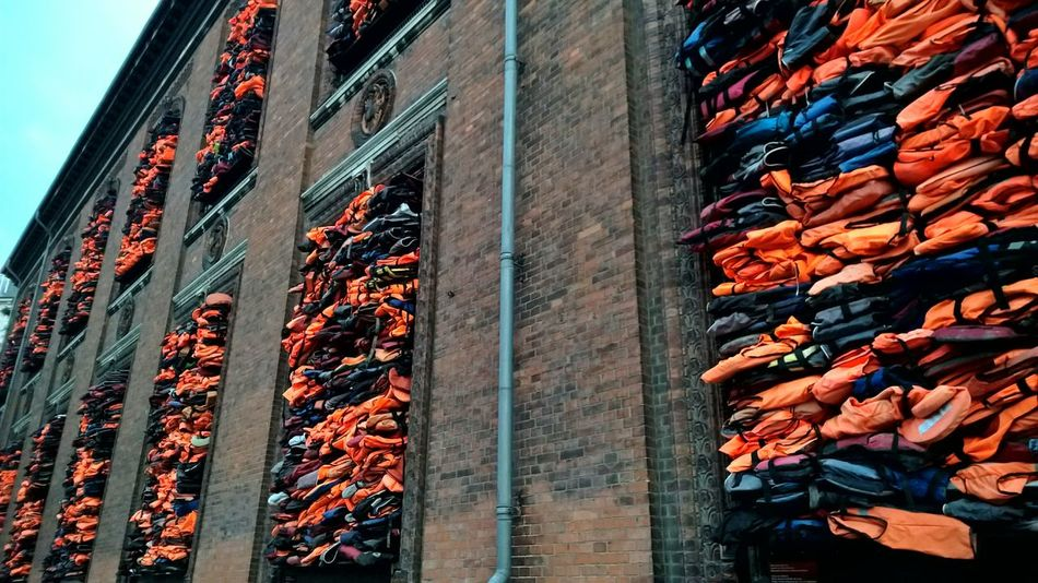 Soleil Levant. The art work consists of a barricade of the windows with more than 3500 life jackets collected from refugees on the Greek island of Lesbos. Ai Weiwei Refugees Life Jacket Life Jackets Lesbos
