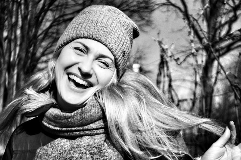 Close-Up Portrait Of Cheerful Woman Against Trees